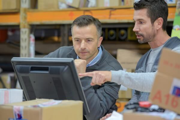 warehouse worker and manager using computer in a warehouse